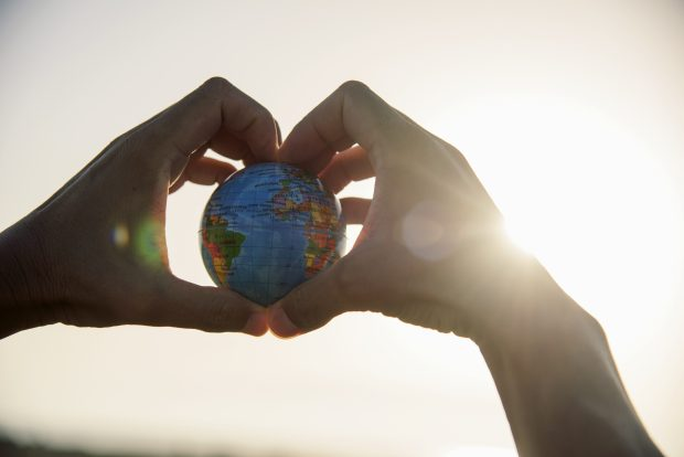 Pair of hands in aheart shape, holding a small Earth globe with sunshine coming in from behind the right hand.