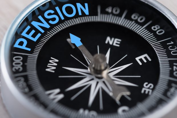 Close up of a compass, with the arrow pointing due north to the word pension.