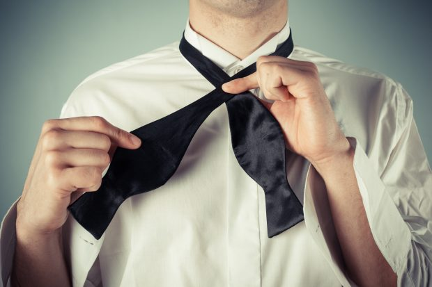 Man in white shirt tying black bow tie
