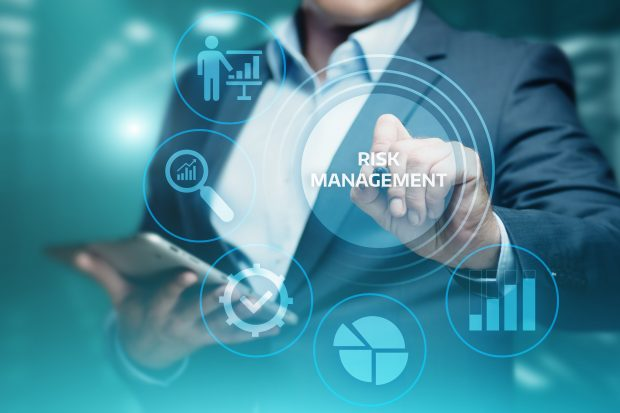 Stock image of man in suit holding a tablet in his right hand and pointing to the words 'risk management' with his left hand