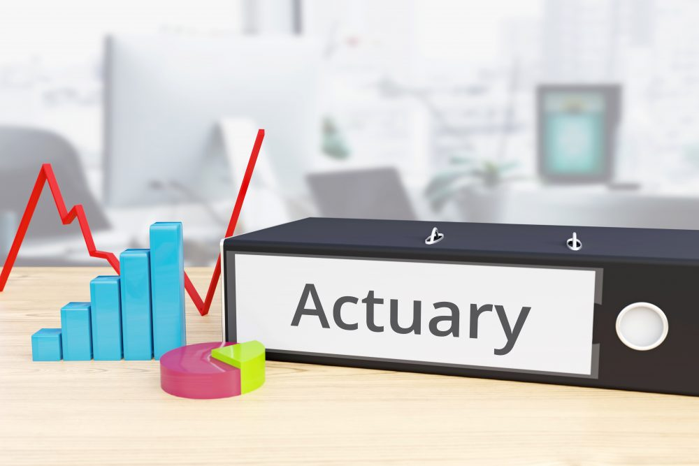 Lever arch file with the word actuary on its spine, on a table next to representations of a pie chart, graph and bar chart.