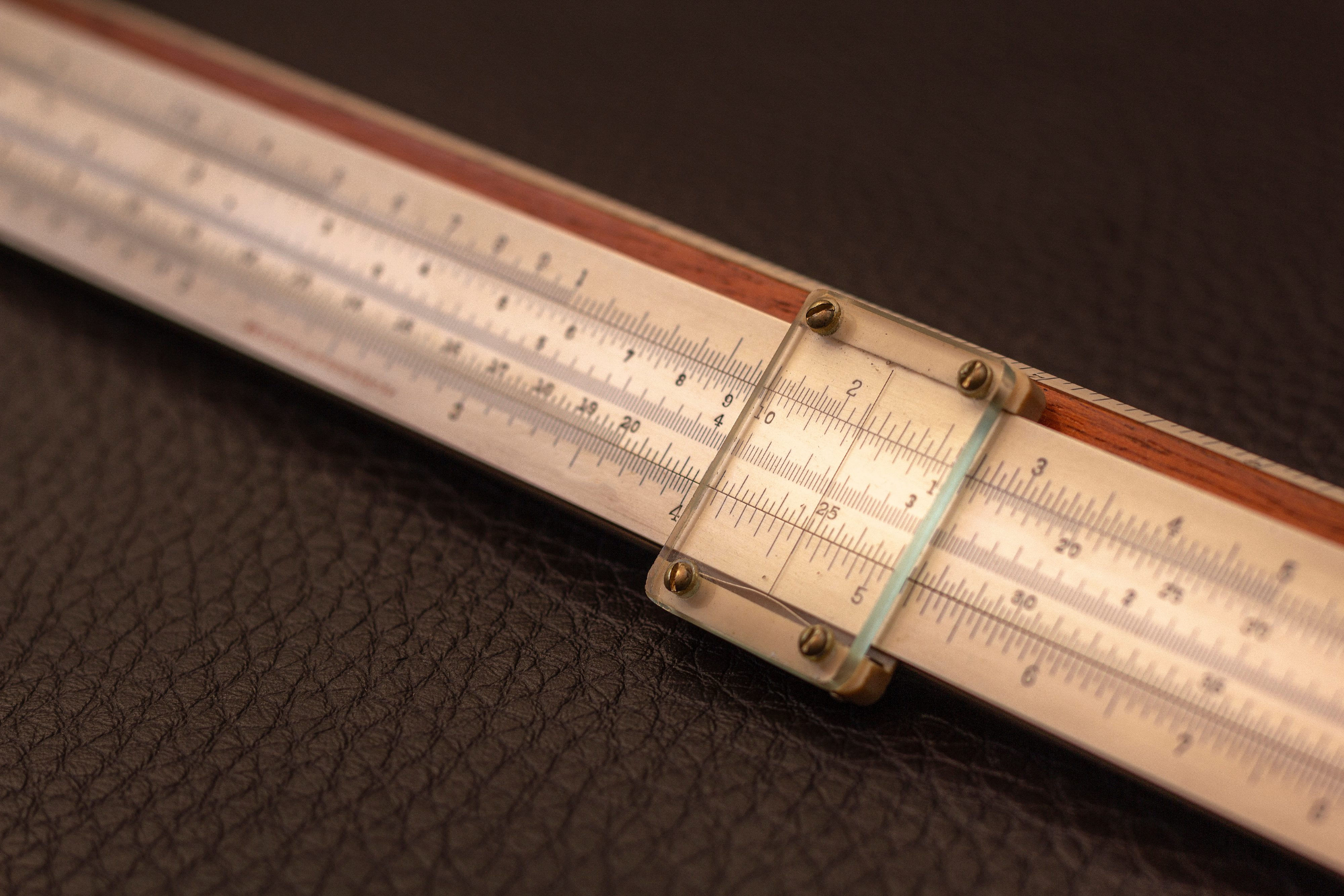 Close up of slide rule from 1915, on a dark background.