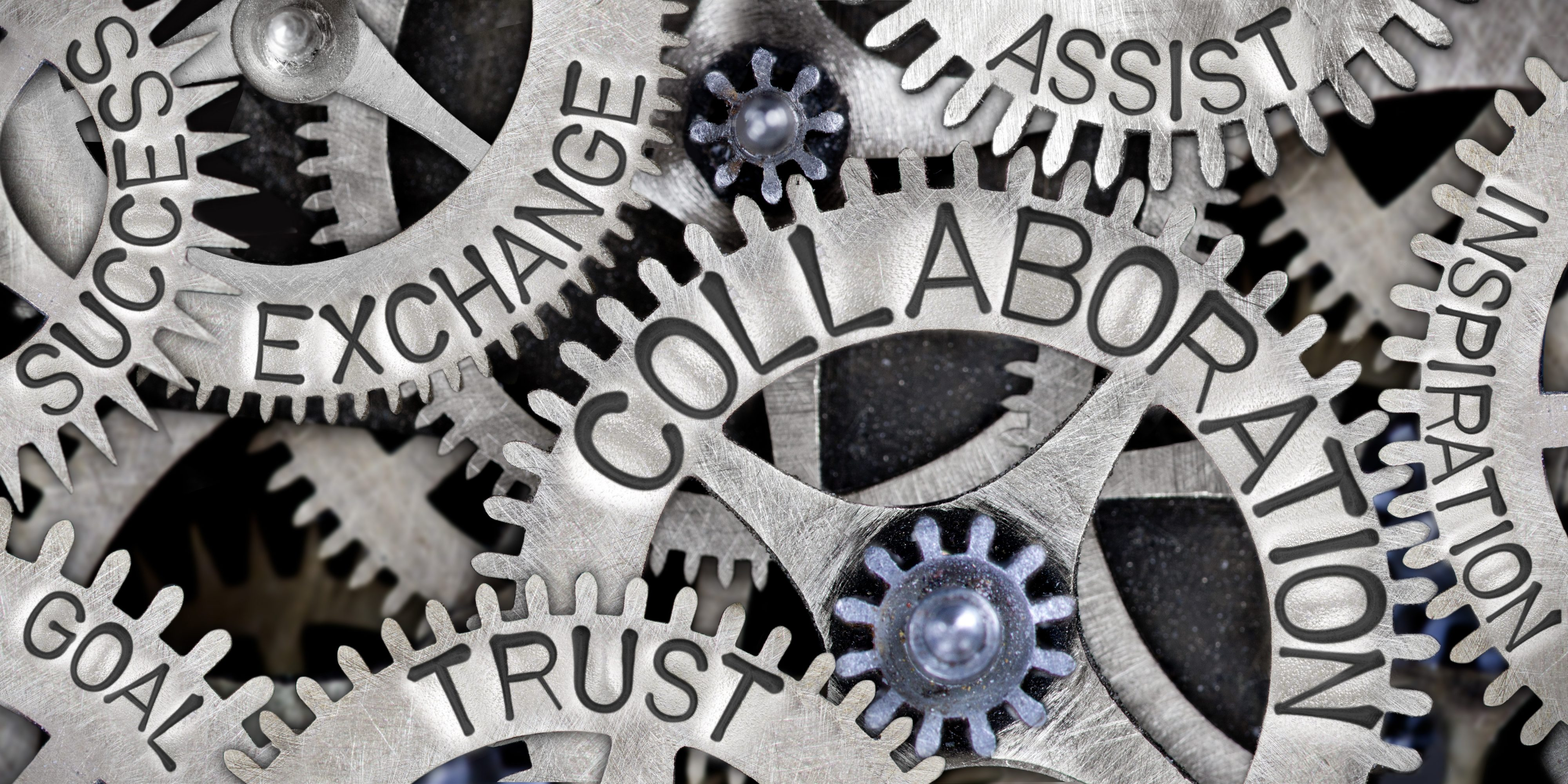 Metal cogs with various words including collaboration, trust, goal, assist, inspiration, exchange and success.