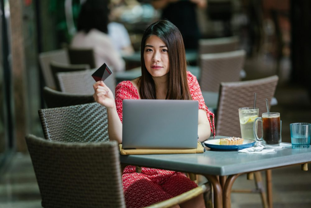 Woman in cafe with laptop and credit card.