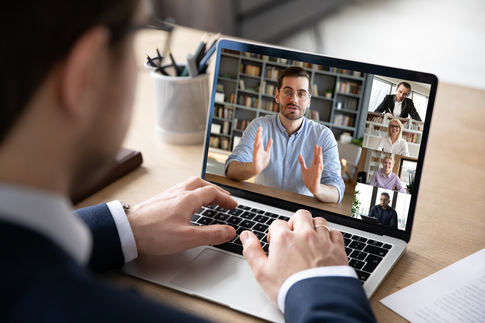 Man joining virtual meeting with other people on his laptop screen.