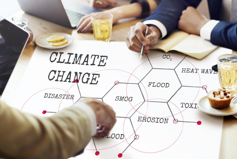 People in a meeting pointing to a large document which has 'climate change' written on it.