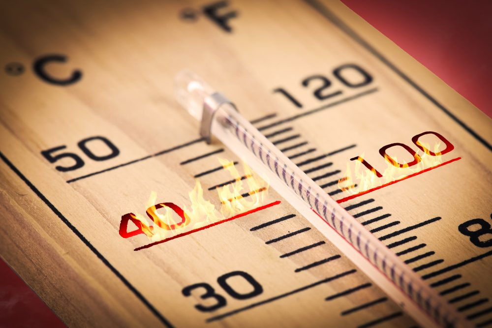 Close up of a wooden temperature gauge with fire at the 40 Celsius mark.
