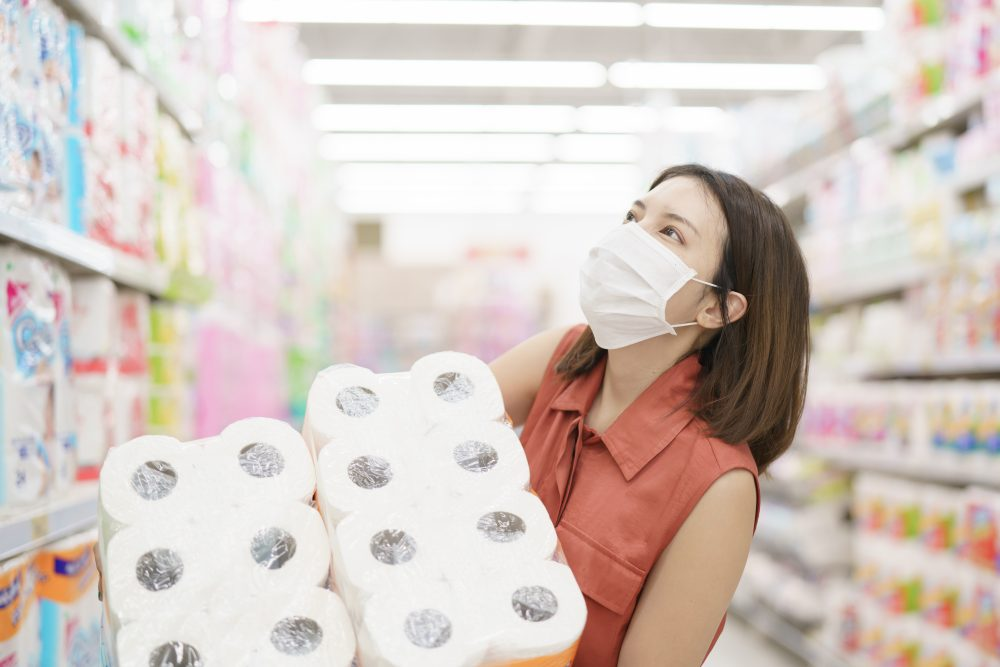 Woman in a supermarket, wearing face mask, carries 2 large packages of toilet rolls.