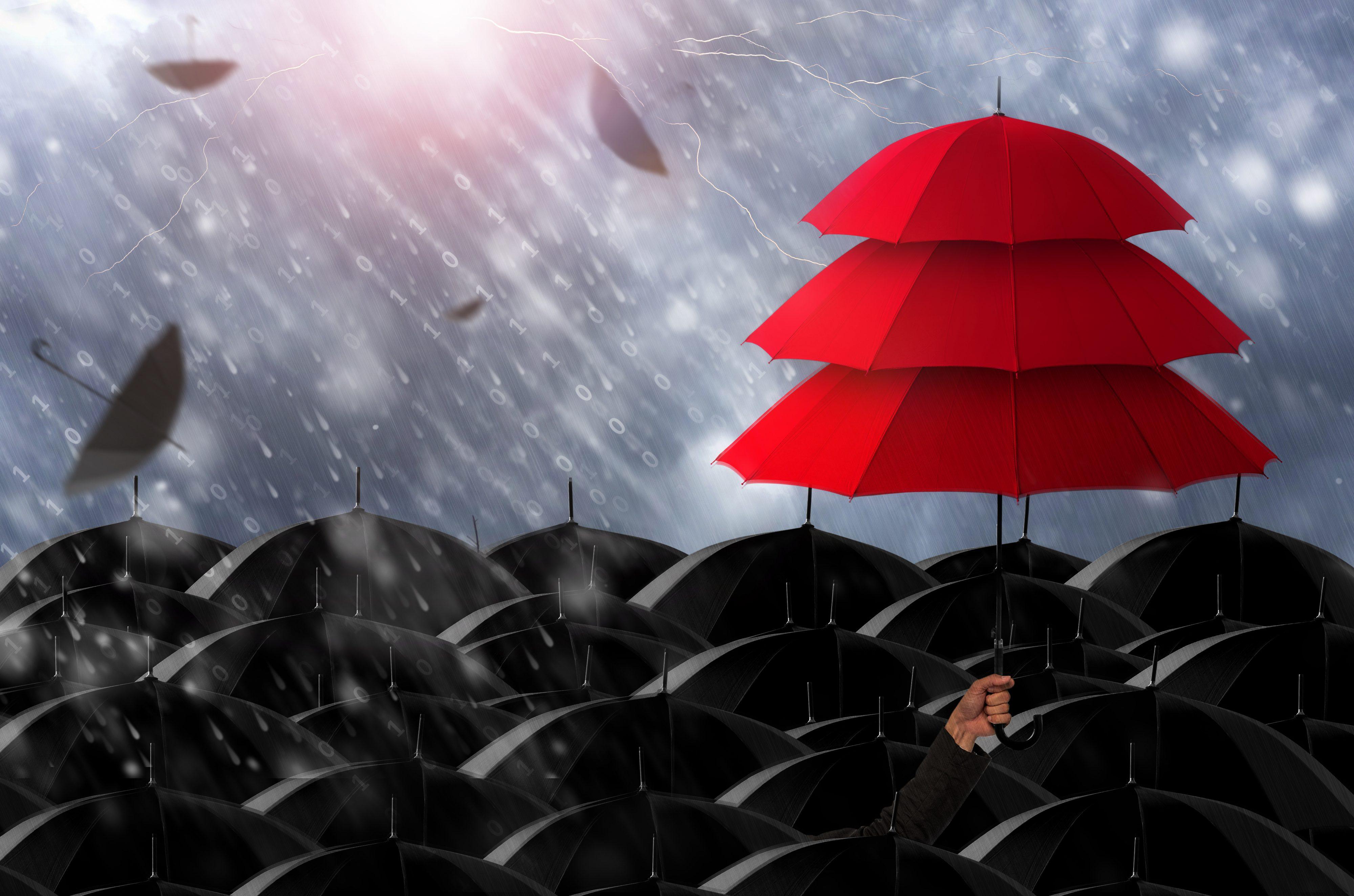 Stack of 3 red umbrellas above loads of black umbrellas in the rain.