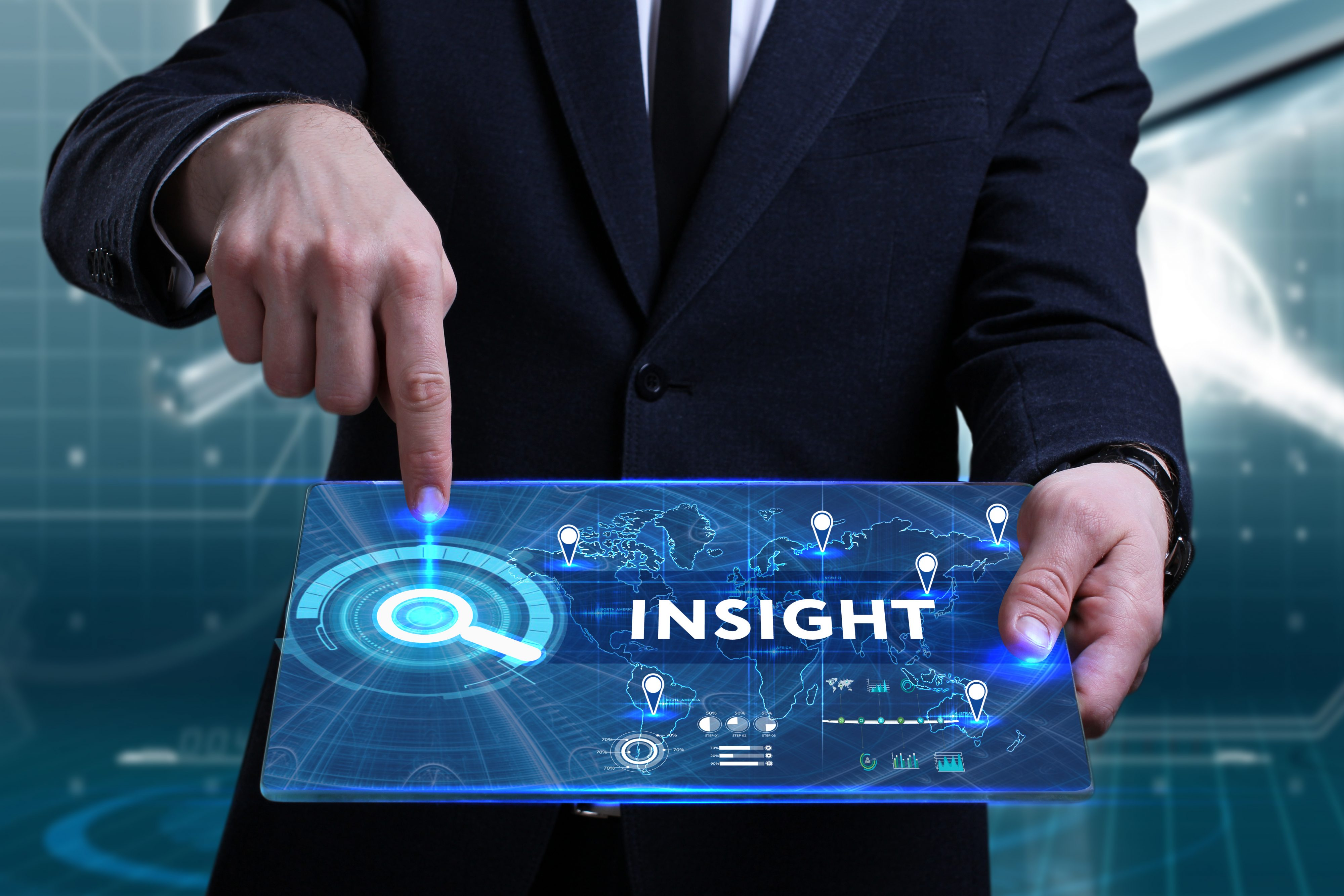 Image of man pointing to the word Insight on a screen he is holding in front of him.
