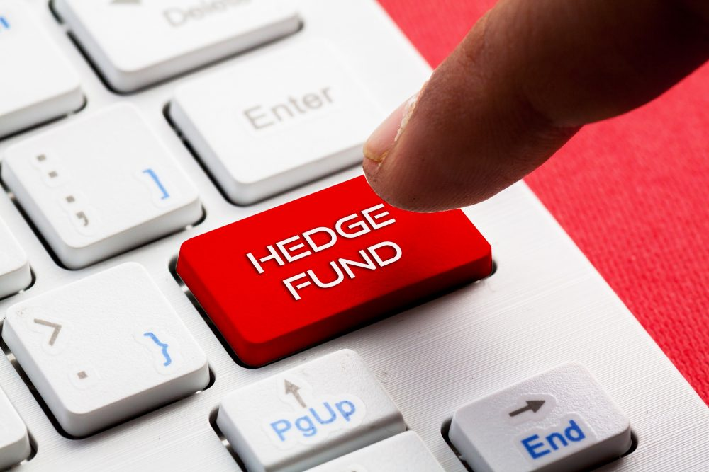 Close up of a man's index finger pointing to a computer button labelled Hedge Fund.
