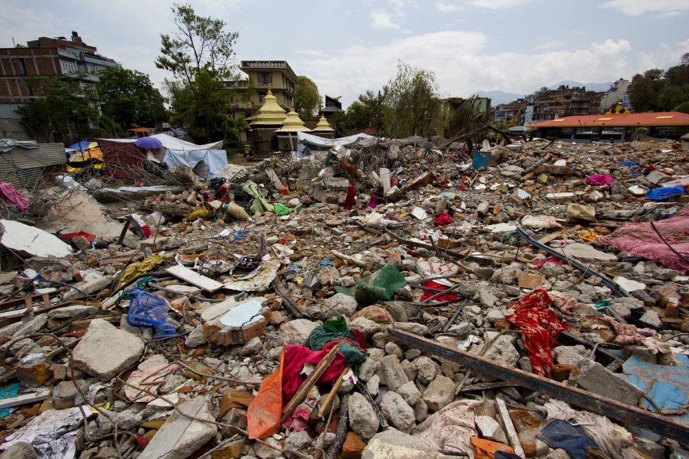 Aftermath of an earthquake. Rubble and clothing strewn over the ground.