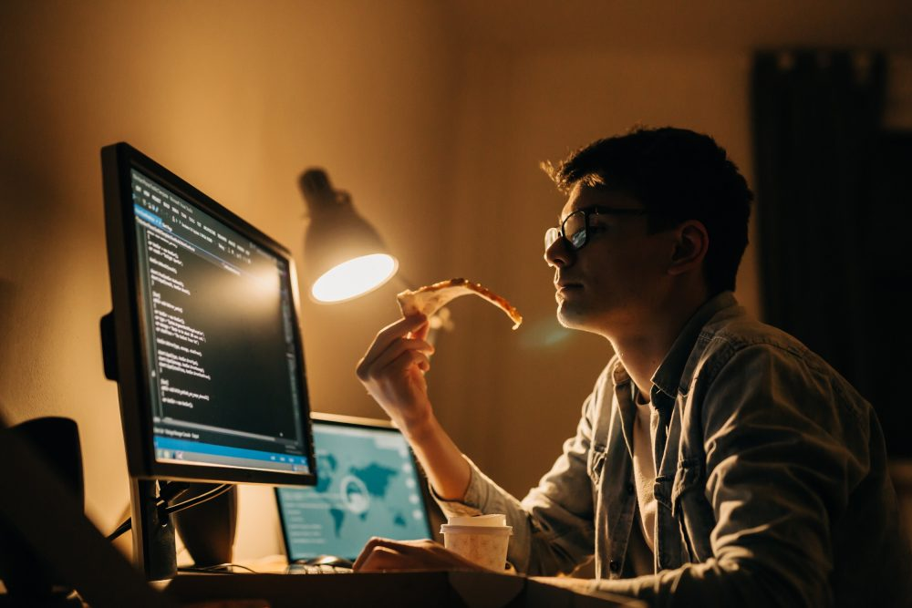 Man working at a computer at night by the light of a desktop lamp.