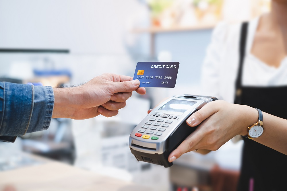 Many using contactless credit card to pay by machine which is being held by a woman.