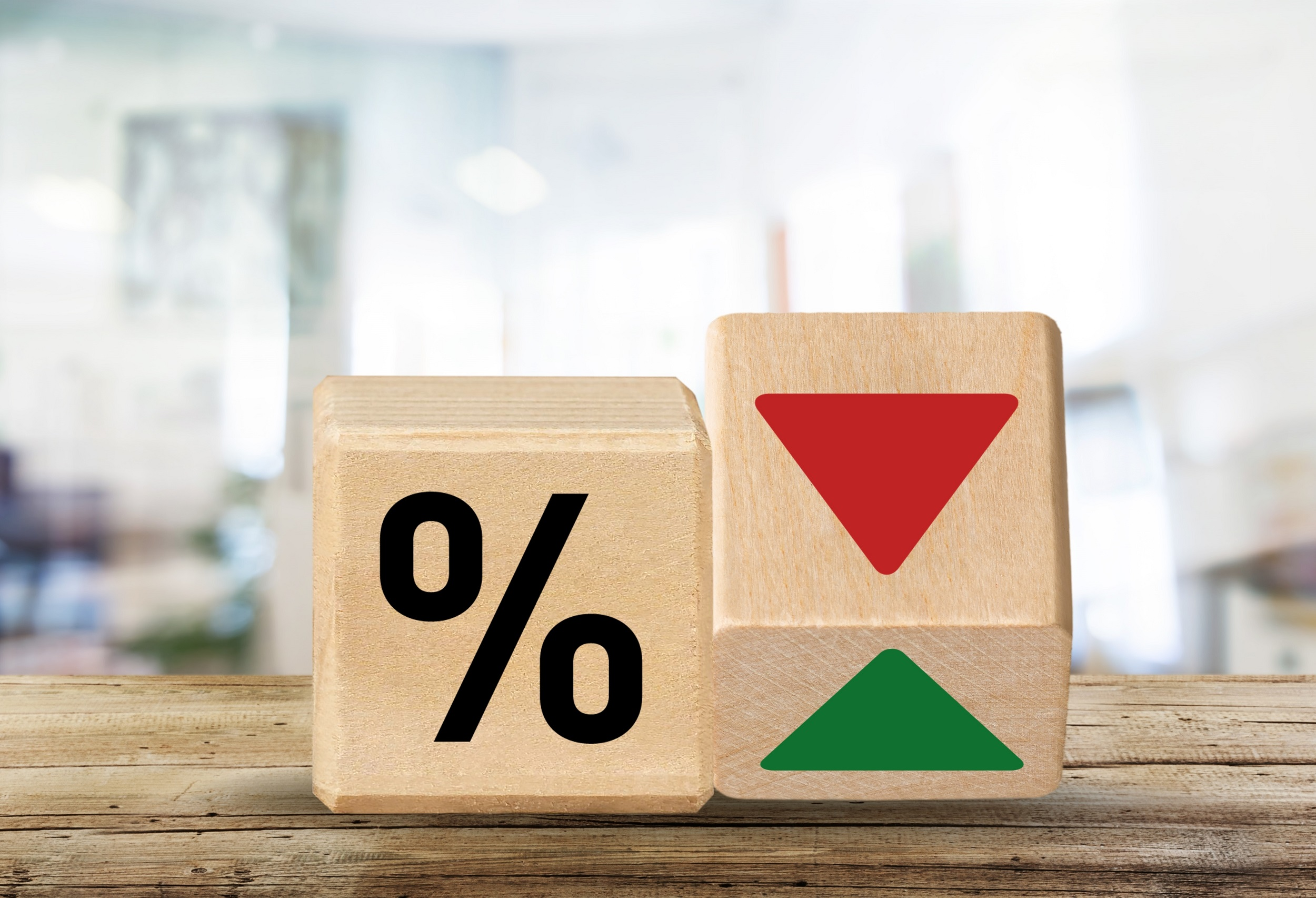 Two small wooden blocks. One shows the percentage symbol and the other is on one of its edges showing a down arrow and an up arrow.