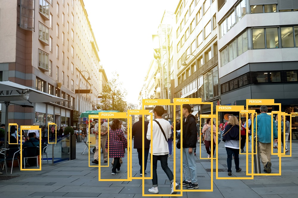 People walking on a high street, being highlighted in yellow boxes from artificial intelligence.