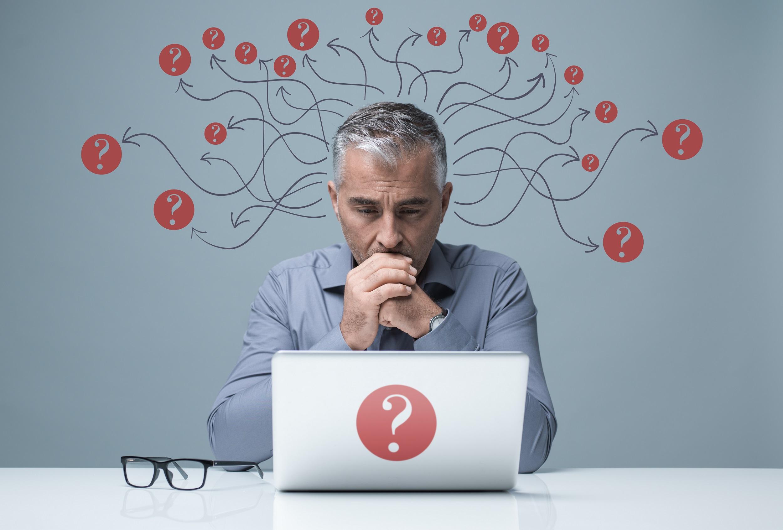 Pensive businessman at laptop.